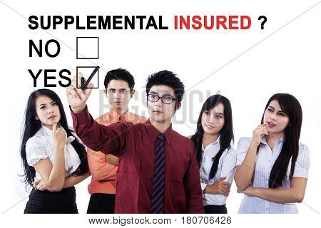 Image of Asian businessman with his team selecting a yes option with a question of supplemental insured on the whiteboard