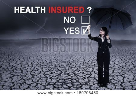 Picture of Asian businesswoman using an umbrella while selecting a yes option to a question of health insured