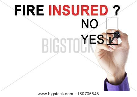 Picture of businessman's hand using a pen while marking in the a yes box with text of fire insured