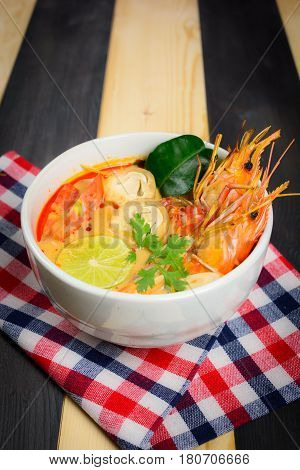 Tom Yum Soup or River Prawn Spicy Sour Soup (Tom Yum Goong) on wooden table with tablecloth Thai local food