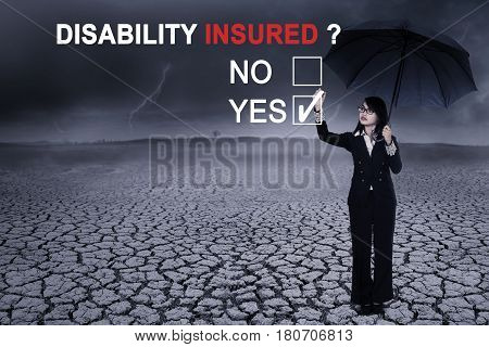 Image of young businesswoman using an umbrella while answering a yes option to a question of disability insured