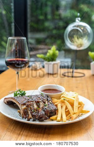 Grilled Barbecued Pork Baby Back Ribs grilled sweet corn and fries on dining table with red wine