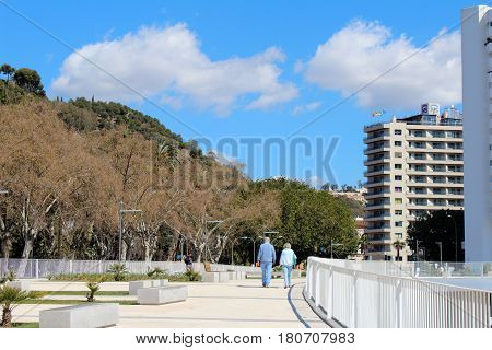 Walking Couple In Seafront Of Malaga Port, Spain