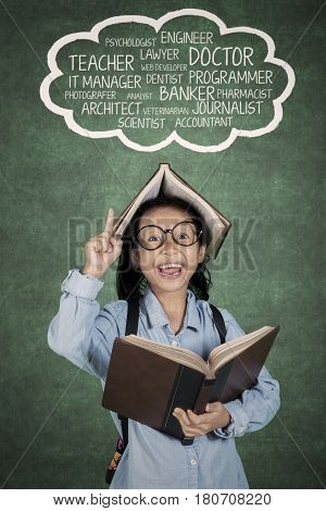 Portrait of elementary student pointing at her dreams on cloud speech while holding a book