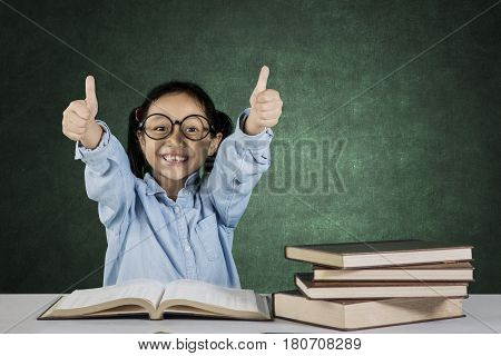 Portrait of elementary student showing ok sign while sitting in front of book on desk