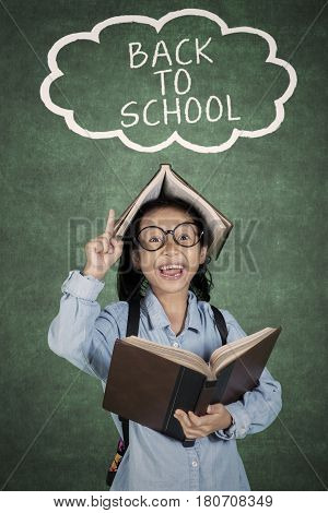 Elementary student holds a book while pointing at back to school text over her head