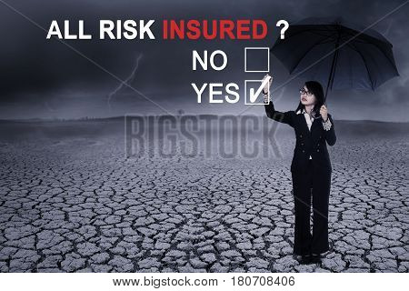 Image of female entrepreneur using an umbrella while selecting a yes option to a question of all risk insured