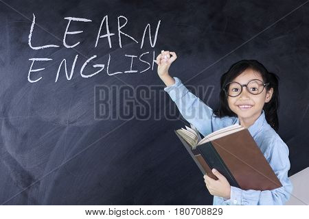 Portrait of little girl holding a book while looking at camera with learn english word on blackboard