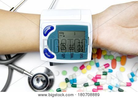 Female hand wearing a Tonometer to measure her heartbeat and blood pressure. Shot with stethoscope and drugs on table