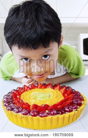 Photo of cute little boy looks hungry with a strawberry pie in the kitchen at home