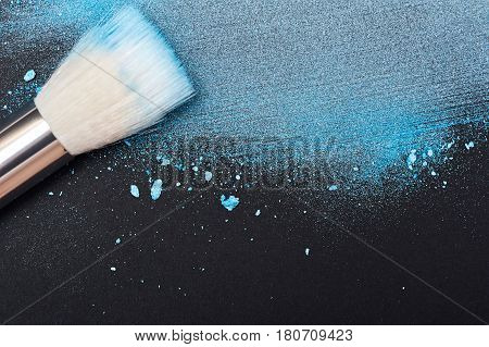 Blue crushed Powder and Make-up Brush on black Surface