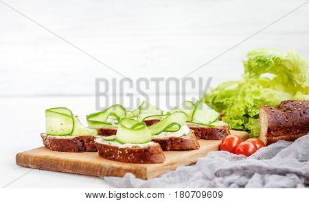 Sandwiches with cheese and cucumber. Lettuce and cherry tomatoes. The concept of food and vegetarianism.
