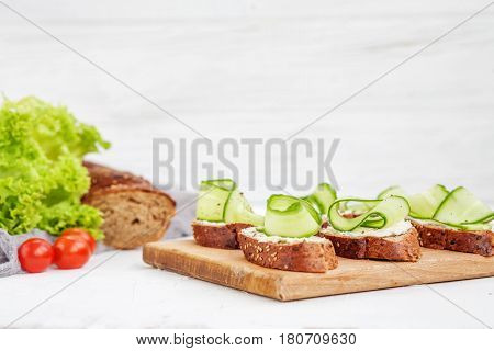 Sandwiches with cheese feta and cucumber. Lettuce and cherry tomatoes. The concept of food and vegetarianism.