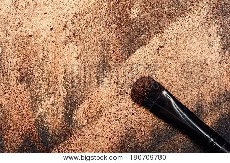 Black Make-up Artist's beauty Brush on golden smeared Surface with Place for Your Text