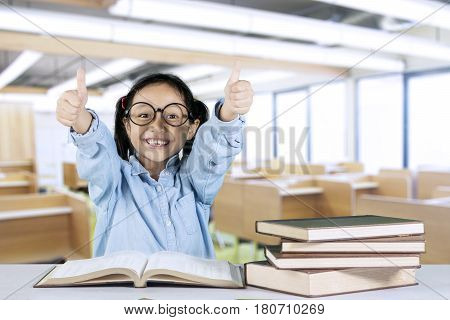 Portrait of smiling little girl showing ok gesture while sitting with book on desk in the classroom