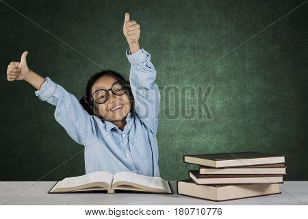 Portrait little student showing ok gesture while sitting in front of book on desk