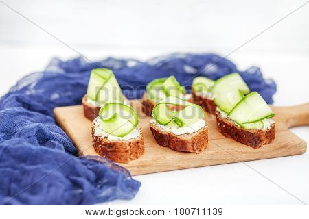 Sandwiches with cheese feta and cucumber on a wooden board. The concept of food and vegetarianism.