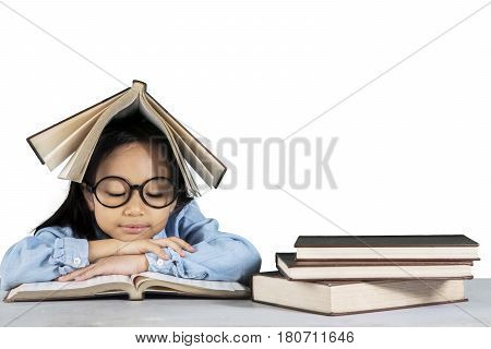 Portrait of primary student reading a book while sitting in studio isolated on white background