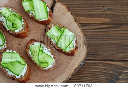 Sandwich with feta cheese and cucumber on a wooden board. Top view. The concept of food and vegetarianism.