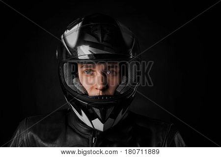 Close up portrait of young mustache biker in motorcycle black helmet and black leather jacket on black background. Moto life concept for advertising sport product. Seller of motorbikes.