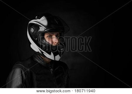Close up side portrait of extreme man in motorcycle helmet. Copy space for advertising moto goods or promotion text. Biker drive his bike for repairing. Motorbiker concept.