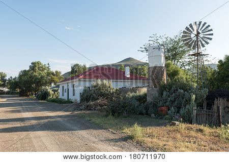 NIEU BETHESDA SOUTH AFRICA - MARCH 22 2017: An early morning street scene with a house and water-pumping windmill in Nieu-Bethesda an historic village in the Eastern Cape Province