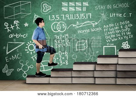 Picture of schoolboy walking on book stair while holding a book with doodle and scribble on chalkboard