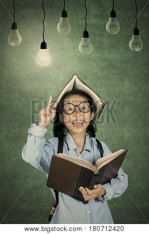 Portrait of schoolgirl gets inspiration with light bulb over her head while holding a book
