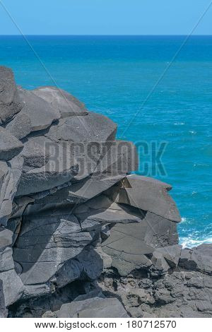 Grey Rock Formation and Blue Ocean: a jagged rock formation with a beautiful blue ocean and light blue sky, in the background