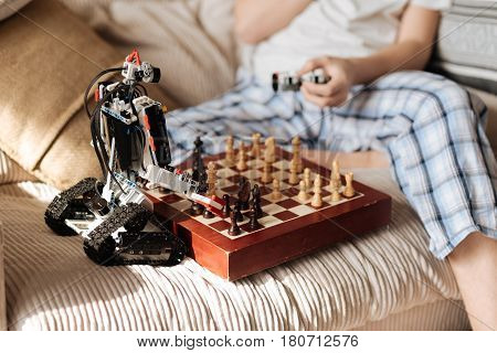 My term. Teenager sitting opposite his toy holding console in left hand, keeping chess between robot and himself