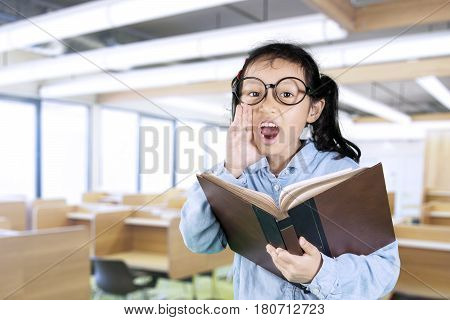 Cute schoolgirl wearing glasses shouting while holding a textbook in the classroom