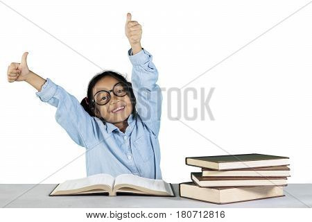 Portrait of schoolgirl showing ok gesture with book on the table while sitting in studio isolated on white background
