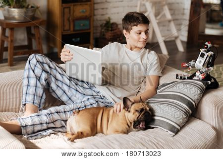 Make a brake. Attractive young brunette lying on the sofa scratching his dog that is yawning on the pillow