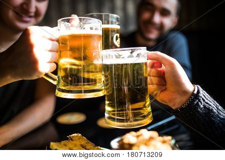 Close Up Of Clanging Glasses Of Beer Of Three Friends In Pub