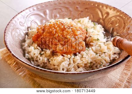 Herby rice with spicy chicken thigh in a bowl