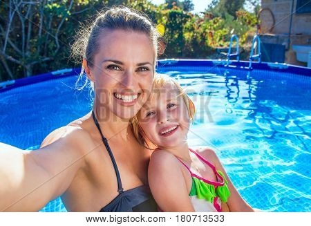 Smiling Mother And Daughter In Swimming Pool Taking Selfie