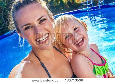 Happy Active Mother And Child In Swimming Pool Taking Selfie
