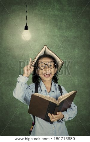 Portrait of little student gets idea while holds a book with light bulb over her head