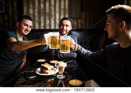 Three Young Men In Casual Clothes Are Smiling And Clanging Glasses Of Beer Together While Sitting In