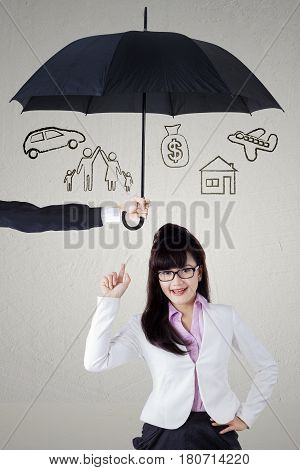 Portrait of a beautiful businesswoman thinking of idea while pointing her dreams under umbrella. dreams insured concept