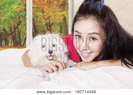 Young woman lying on the bed with an embracing cute maltese dog in autumn season
