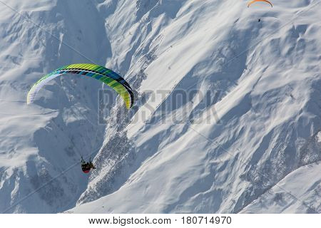 Parachute Sky-diver Flying In Clouds Above Mountains With Fresh Snow On Sunny Winter Day In The Ski
