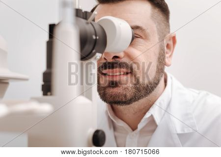 Professional doctor. Delighted professional male oculist looking into special lenses and examining the eyesight of his patient while enjoying his job