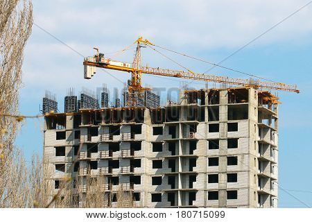 High crane on the construction of a multifamily urban residential building