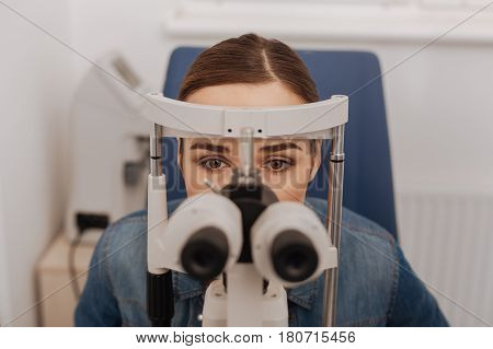 Test for myopia. Pleasant attractive young woman sitting in the chair looking into binoculars while having an eye test for myopia