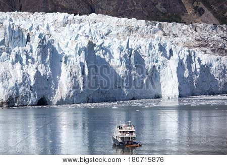 The small boat drifting by the glacier in Glacier Bay national park (Alaska).