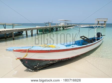 The wooden motorboat on a beach of Roatan Island (Honduras).
