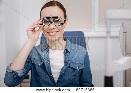 Interesting procedure Delighted beautiful young woman smiling and fixing the eye test glasses while having the examination of her eyesight