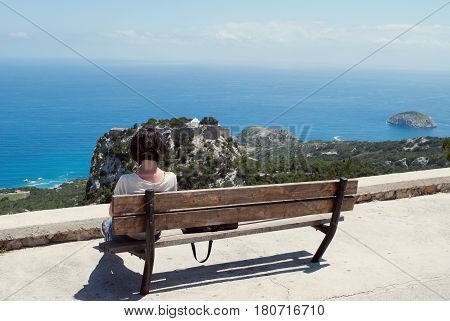 The girl rests on a bench and admires the sea