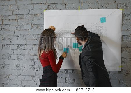Co working of two young architect working on new building project over time. Man and woman colleagues work are preparing presentation of business center in the office. Architecture drawings on wall